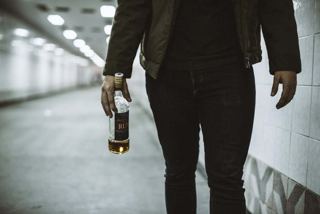 Alcoholic Homeless Holding Liquor Bottle
